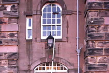 Cleaning a multi-paned wooden sash and case arched window with a waterfed pole