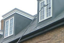 Using a waterfed pole to clean a multi-paned dormer window